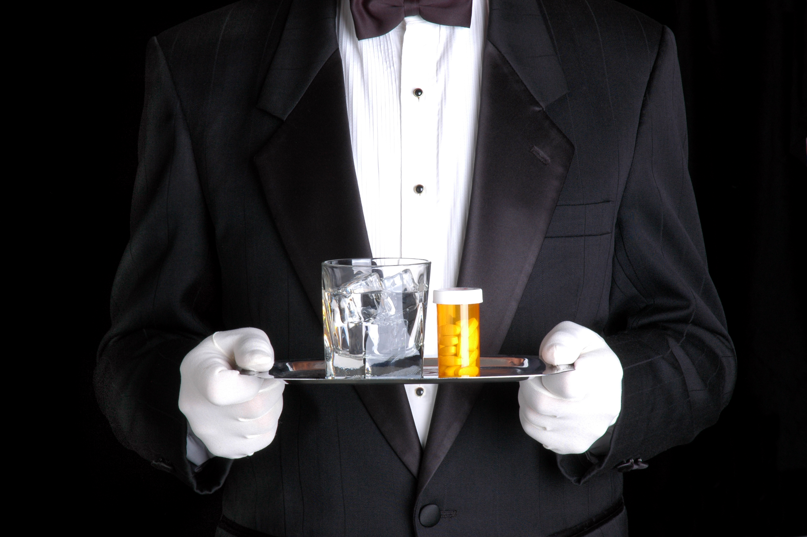 Man Holding Pills and Glass of Water on Silver Tray